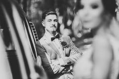Gerade verheiratetes Paar im Retro- Luxusauto an ihrem Hochzeitstag stockbild