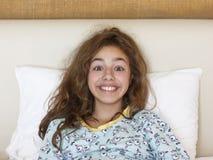 Gerade waches hübsches Jugendlichmädchen mit lustigem Gefühlgesicht und dem wilden Haar auf dem Bett lizenzfreies stockbild