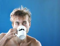Gerade wachte auf und zerzauste den Mann, der frischen Kaffee oder Tee vom Becher mit dem gemalten schwarzen Schnurrbart, Wochent stockfoto