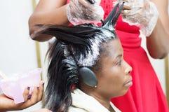 Geraderichten des Haares einer jungen Dame am Friseursalon stockfoto