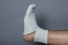 Gerades Bein mit einem großen Loch in der Socke Stockbild