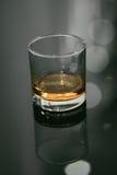 Gerades Whisky-Glas auf schwarzer Tabelle mit Reflexion stockbilder