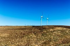Geradores sustentáveis verdes da eletricidade da turbina do poder do moinho de vento da energia em Rolling Hills com nuvens e o c Foto de Stock Royalty Free