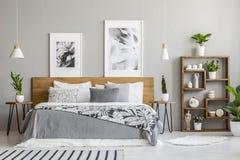 Geral modelado na cama de madeira entre tabelas com as plantas no interior do quarto com cartazes Foto real foto de stock royalty free