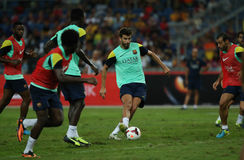 Gerald Pique. KUALA LUMPUR - AUGUST 09: Barcelona Football Club player Gerald Pique passes the ball during training session at the Bukit Jalil National Stadium Royalty Free Stock Photography