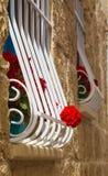 Gerani rossi sulla finestra con le barre, Malta Fotografia Stock Libera da Diritti