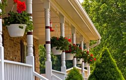 Geranium pots hanging on porch. A view of hanging pots of red geraniums hung along a front porch on a small house in the country Stock Images