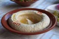 Geranselde Hummus in een plaat Stock Afbeelding