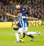Gerard Pique. And Simao in action during the Spanish League match between FC Barcelona and RCD Espanyol, 4 - 0, on January 6, 2013, in Barcelona, Spain Royalty Free Stock Image