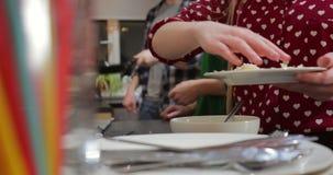 Geraspte kaas die aan een kom worden toegevoegd stock footage