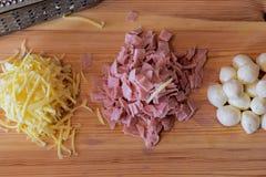 Geraspte kaas, gehakte ham, ballen van mozarella en rasp op houten achtergrond royalty-vrije stock afbeeldingen