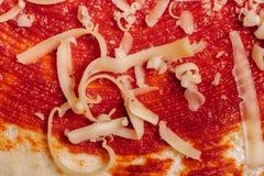 Geraspte kaas voor pizza dicht omhoog op ketchup met een laag bedekt deeg royalty-vrije stock afbeelding
