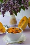 Geraspte pompoensalade met rozijnen l op een lilac lijst met een boeket van lilac bloemen Concept: ruw voedsel, veganism, vegetar stock foto's