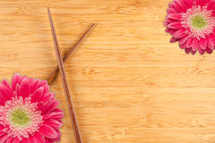 Gerber Daisy and Chopsticks on a Bamboo Background Stock Photos