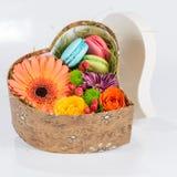 Gerbera et macaron de fleur dans la boîte en forme de coeur Image stock