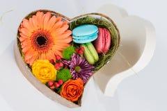 Gerbera et macaron de fleur dans la boîte en forme de coeur Photo stock