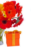 Gerbera fresh  flowers in glass vase with gift Royalty Free Stock Image