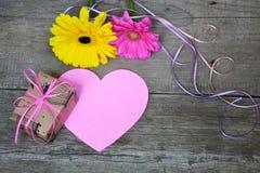 Gerberas цветут с подарочной коробкой, бумажным сердцем и покрашенными лентами на древесине стоковая фотография rf