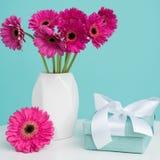 Gerberas cor-de-rosa escuros em um vaso em uma tabela com presente bonito Conceito feliz do ` s a Dinamarca da mãe Imagem de Stock