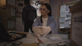Gerechtelijke wetenschapperdame die op handschoenen zetten en de bewijsmateriaalkogel onderzoeken stock videobeelden