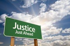 Gerechtigkeits-Just Ahead Green-Verkehrsschild und Wolken Lizenzfreies Stockbild