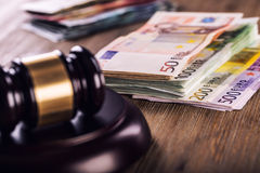 Gerechtigkeits- und Eurogeld Fünf, 10 und fünfzig Eurobanknoten Gerichtshammer und gerollte Eurobanknoten Darstellung von Korrupt Stockfoto