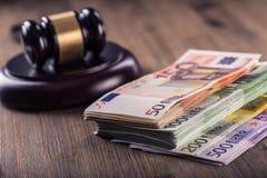 Gerechtigkeits- und Eurogeld Fünf, 10 und fünfzig Eurobanknoten Gerichtshammer und gerollte Eurobanknoten Darstellung von Korrupt Stockbilder