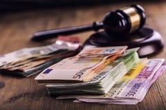 Gerechtigkeits- und Eurogeld Fünf, 10 und fünfzig Eurobanknoten Gerichtshammer und gerollte Eurobanknoten Darstellung von Korrupt Stockfotografie