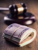 Gerechtigkeits- und Eurogeld Fünf, 10 und fünfzig Eurobanknoten Gerichtshammer und gerollte Eurobanknoten Darstellung von Korrupt Stockbild