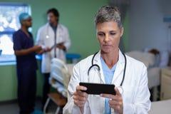 Gereifte Ärztin, die Handy in der Klinik am Krankenhaus verwendet lizenzfreie stockfotos