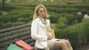 Gereizte Frau, die sitzende Bank des Babys, werfende Einkaufstaschen, Müdigkeit erwartet stock video