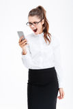 Gereizte wütende junge Geschäftsfrau, die Handy und das Schreien verwendet Stockbilder