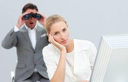 Gerente com os binóculos que olham seu colega Fotografia de Stock Royalty Free
