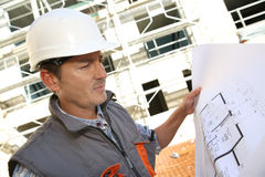 Gerente da construção no local que verifica o plano foto de stock