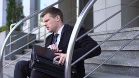 Gerente de empresa masculino infeliz que senta o prédio de escritórios exterior, desespero da destituição video estoque