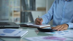 Gerente de empresa que conta a calculadora e que escreve o caderno, relatório de vendas, projeto vídeos de arquivo