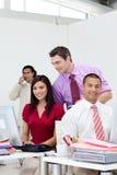 Gerente de sorriso que verific seu trabalho da equipe Imagens de Stock