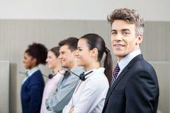 Gerente de sorriso Standing In Row com equipe Imagens de Stock Royalty Free