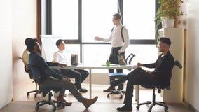 Gerente de vendas novo na posição branca da camisa com seu relatório na reunião de negócios video estoque