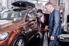 Gerente de vendas que diz seu cliente constante próspero sobre o carro novo fotos de stock