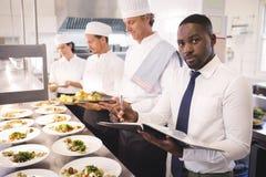 Gerente do restaurante com seu pessoal da cozinha fotografia de stock royalty free