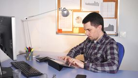 Gerente do trabalhador de escritório que senta-se em seu lugar de trabalho, usando um portátil vídeos de arquivo