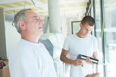 Gerente do vidraceiro que inspeciona o vidro imagens de stock