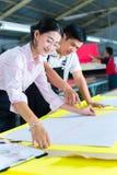 Gerente e desenhista asiáticos de produção na fábrica Fotografia de Stock