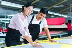 Gerente e desenhista asiáticos de produção na fábrica Fotografia de Stock Royalty Free