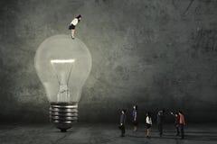 Gerente fêmea com lâmpada e empregados Imagens de Stock