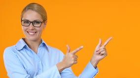 Gerente fêmea de sorriso que aponta os dedos no molde alaranjado do fundo para o texto video estoque
