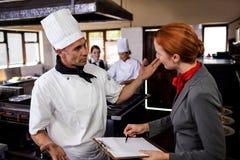 Gerente fêmea e cozinheiro chefe masculino que interagem um com o otro na cozinha foto de stock royalty free