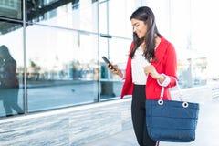 Gerente fêmea Using Mobile Phone após o trabalho foto de stock