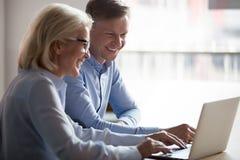 Gerente feliz e cliente que têm a conversação em encontrar o portátil fotos de stock